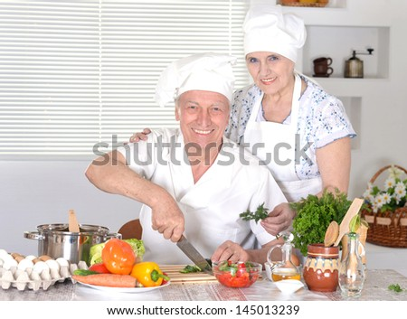 elderly couple preparing a tasty vegetable salad - stock photo