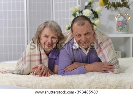 elderly couple resting on the couch - stock photo