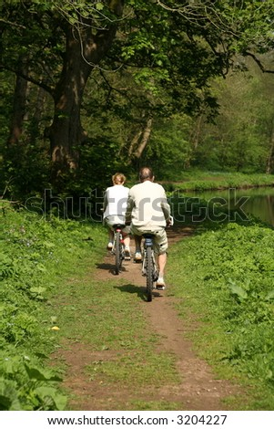 ELDERLY COUPLE RIDING BIKES - stock photo