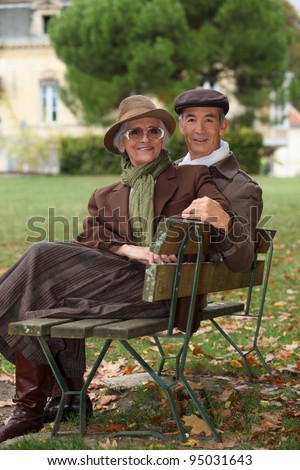 Elderly couple sat on bench