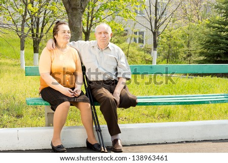 Elderly couple sitting close together on a park bench enjoying the sunshine - the husband has one leg amputated and is using crutches - stock photo