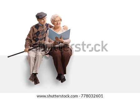 Elderly couple sitting on a panel and reading a book isolated on white background