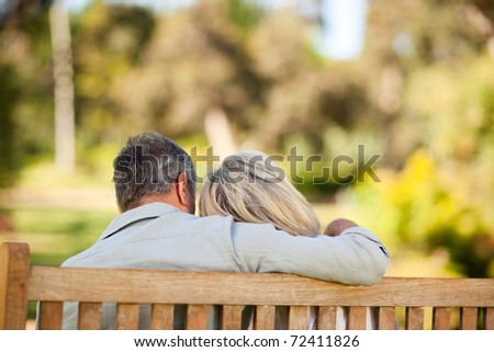 Elderly couple sitting on the bench with their back to the camera - stock photo