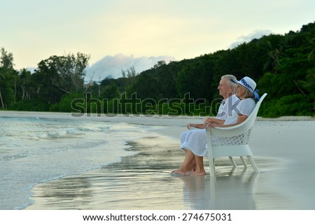 Elderly couple sitting on the shore and looks at sea - stock photo