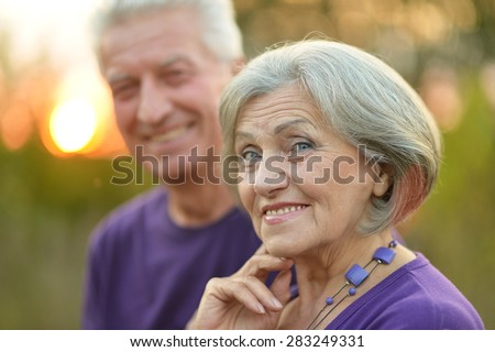 Elderly couple smiling together over natural background - stock photo