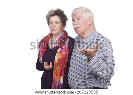 Elderly couple standing with question marks on their faces - stock photo
