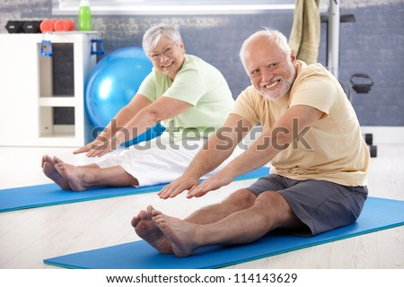 Elderly couple stretching in the gym. - stock photo