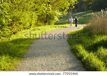 elderly couple take a stroll in the park - stock photo
