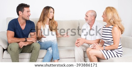 Elderly couple talks with younger couple - stock photo