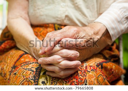 Elderly couple - the caring husband putting his hand on his wife's hands, showing love and support in hard times. - stock photo