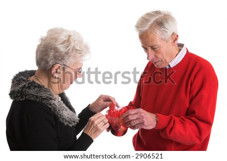 Elderly couple together holding a box of chocolate