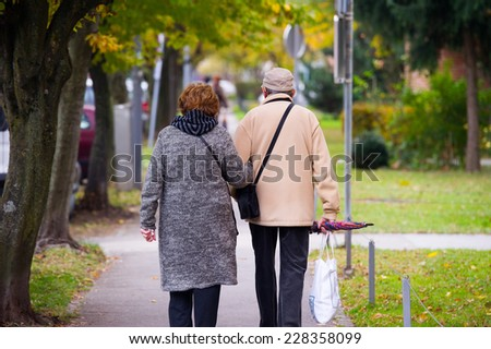 Elderly couple walking in the city. - stock photo