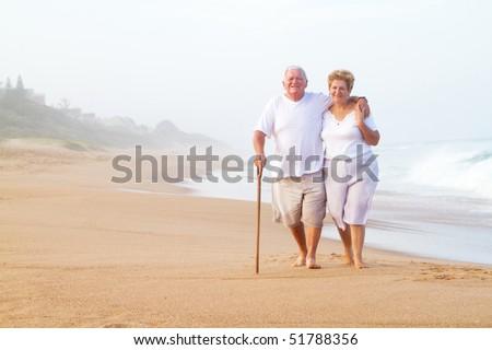 elderly couple walking on beach - stock photo