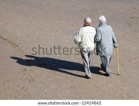 Elderly couple walking on beach on sunny day - stock photo