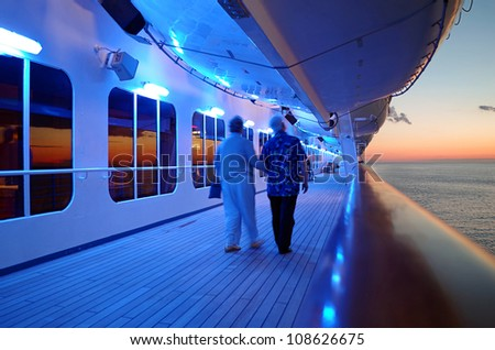 Elderly Couple Walking On Cruise Ship Deck in Evening - stock photo