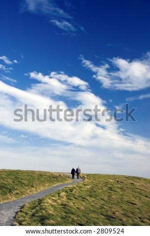 elderly couple walking on path - stock photo