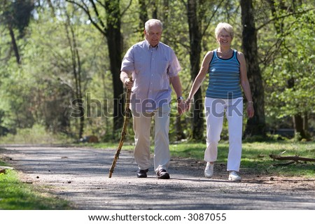 Elderly couple walking through the parc hand in hand - stock photo