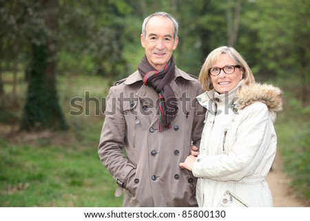 Elderly couple walking through woods - stock photo