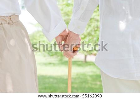 Elderly couple who grips walking stick - stock photo