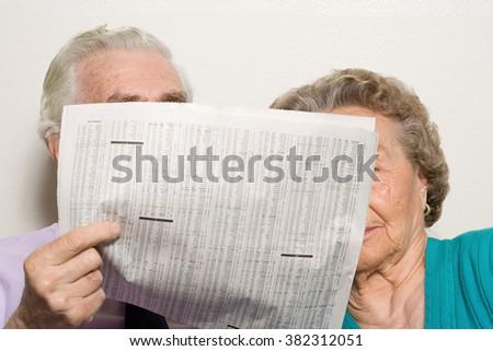 Elderly couple with newspaper - stock photo