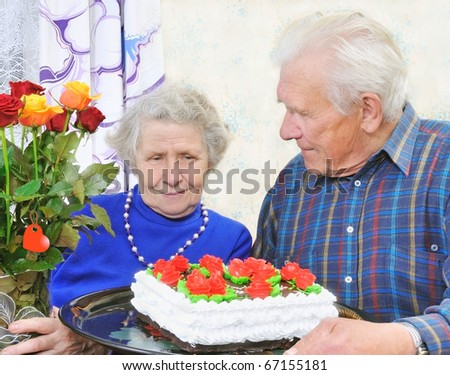 elderly couple with tasty big cake and roses - stock photo