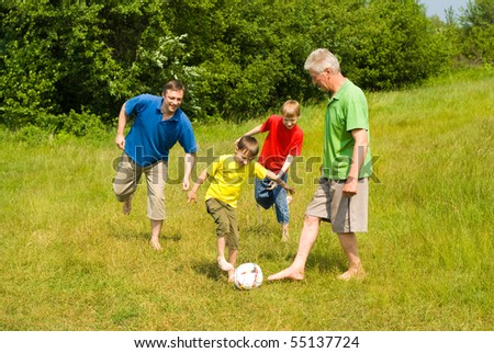 elderly couple with their grandchildren playing soccer - stock photo