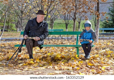 Elderly disabled grandfather watching over his young grandson as the two sit on a wooden bench in the park together with the old man reading a book while the youngster reads on a tablet computer