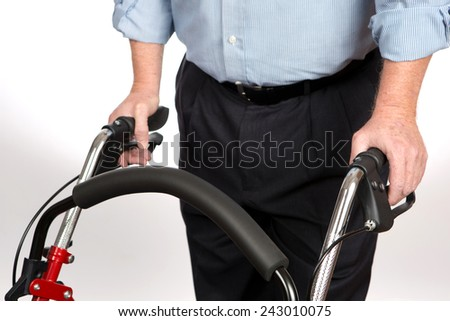 Elderly disabled man is using a walker to keep from falling and to give him stability as he walks alone for independent living. - stock photo