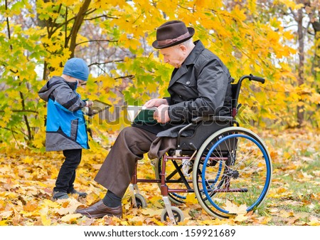 Elderly disabled man sitting reading a book in a wheelchair enjoying a day out in an autumn park with his little grandson who is standing playing with a tablet computer - stock photo