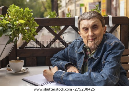 Elderly disabled man with cerebral palsy in outdoor cafe. - stock photo
