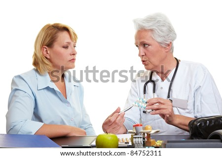 Elderly doctor offering medication to female patient