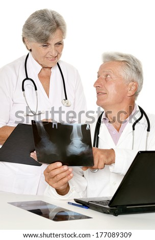 Elderly doctors with a laptop examining x ray - stock photo