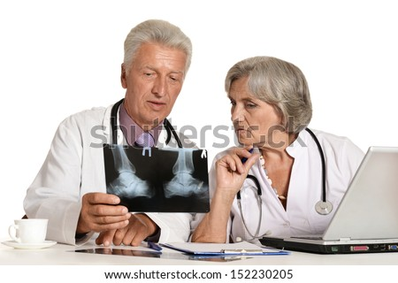 Elderly doctors with a laptop looking at x-ray on a white - stock photo