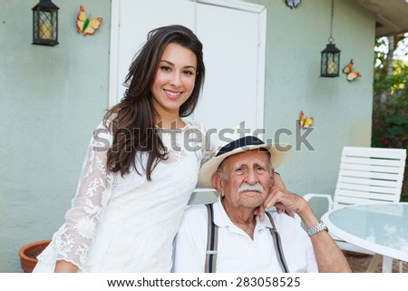 Elderly eighty plus year old man with granddaughter in a outdoor home setting. - stock photo