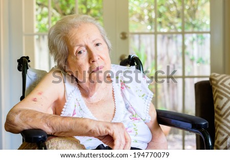 Elderly eighty plus year old woman in a wheel chair in a home setting. - stock photo