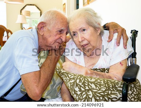 Elderly eighty plus year old woman in a wheel chair in a home setting with her husband. - stock photo