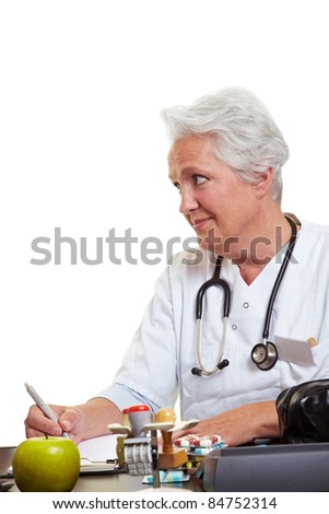 Elderly female doctor at desk listening to patient - stock photo