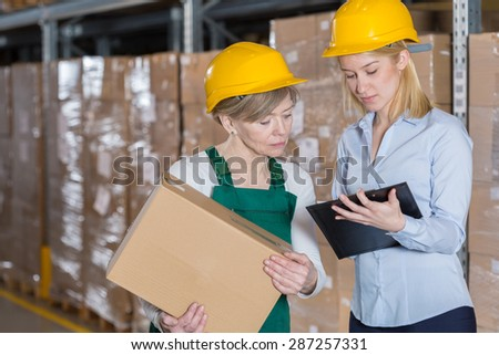Elderly female factory worker and young pretty boss - stock photo