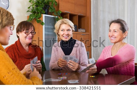 Elderly female having fun with pack of cards indoor - stock photo