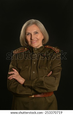 Elderly female soldier on a black background - stock photo