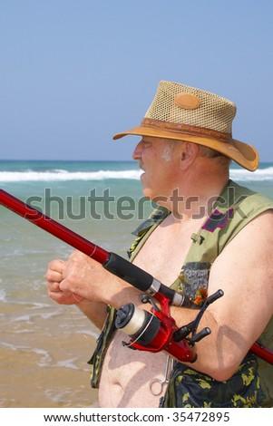 Elderly fisherman at the seaside - stock photo