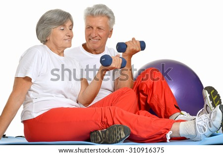 Elderly fit couple having a rest on a floor of gym on white background