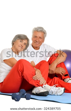 Elderly fit couple having a rest on a floor of gym on white background - stock photo