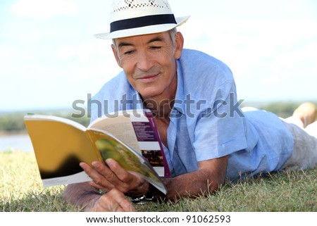 elderly gentleman lying on grass reading tourist guide - stock photo