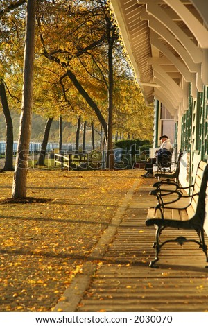 Elderly gentleman sitting on a bench at a sea side train station. (White Rock, B.C.) - stock photo