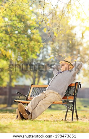 Elderly gentleman sitting on a bench in park on a sunny day - stock photo