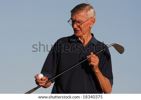 Elderly golfer inspecting his golf ball and club - stock photo