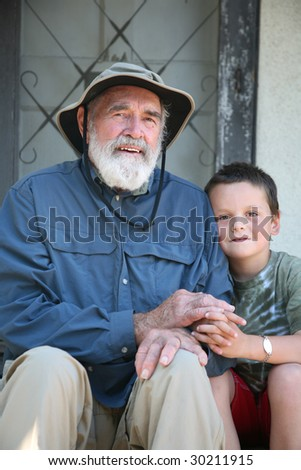 Elderly grandfather with his grandson sitting on a home porch - stock photo