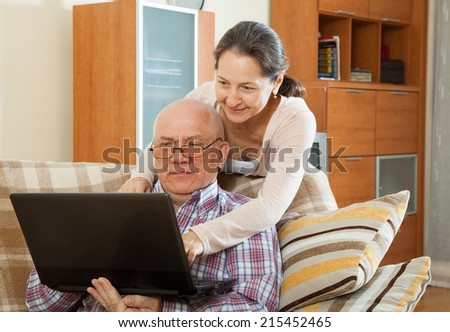 elderly gray-haired man and mature woman working at  laptop on  sofa