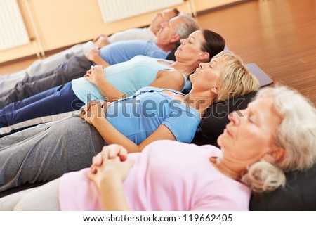 Elderly group doing neditation and relexation in a fitness center - stock photo